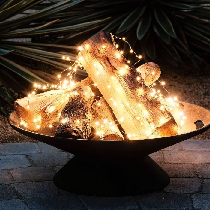 faux fire pit backyard lighting ideas logs arranged in metall pit wrapped with led fairy lights