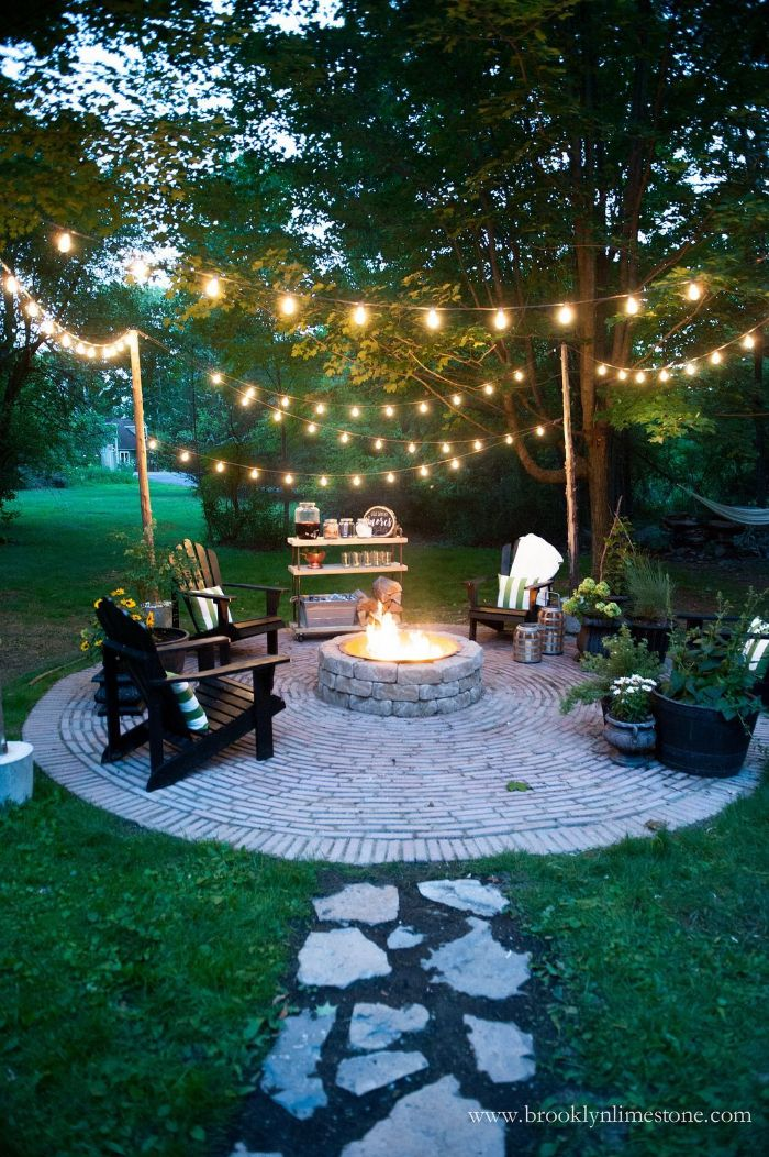 fire pit lounge are and bar table around it outdoor lighting ideas strings of lights hanging from the trees above it