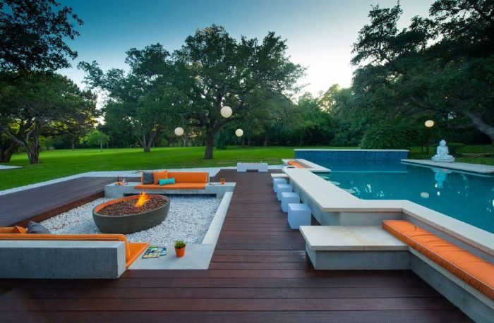 fire pit surrounded by stone benches with orange cushions backyard pool ideas wooden floor