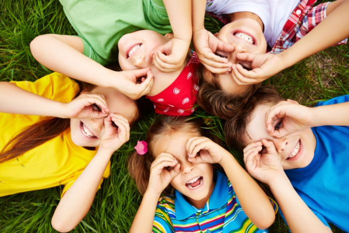 five kids laying on the grass in a circle things to do outside making binoculars with their hands smiling