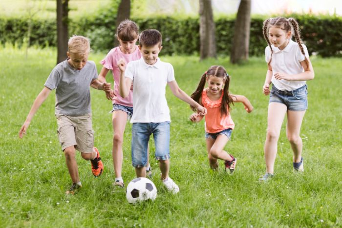 five kids playing football on field covered with green grass things to do outside soccer