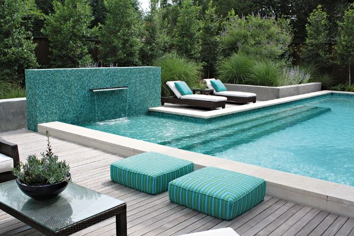 fountain and a pool with blue cushions and throw pillows on lounge chairs modern pool designs