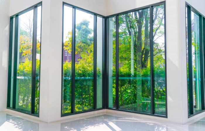four tall glass windows overlooking green garden with black frames door installation