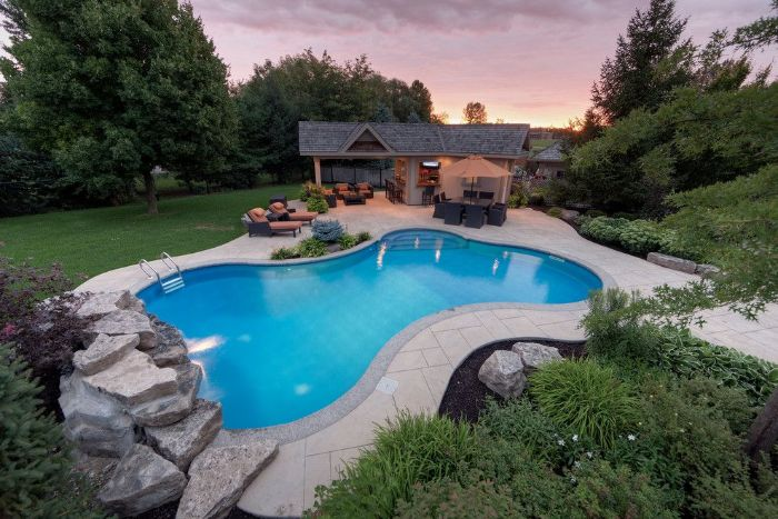 free flow pool in the back of small house pool landscaping ideas surrounded by rocks trees and bushes