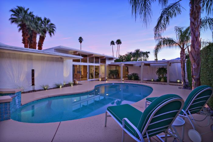free flow pool with two lounge chairs next to it small backyard pool ideas house surrounded by palm trees