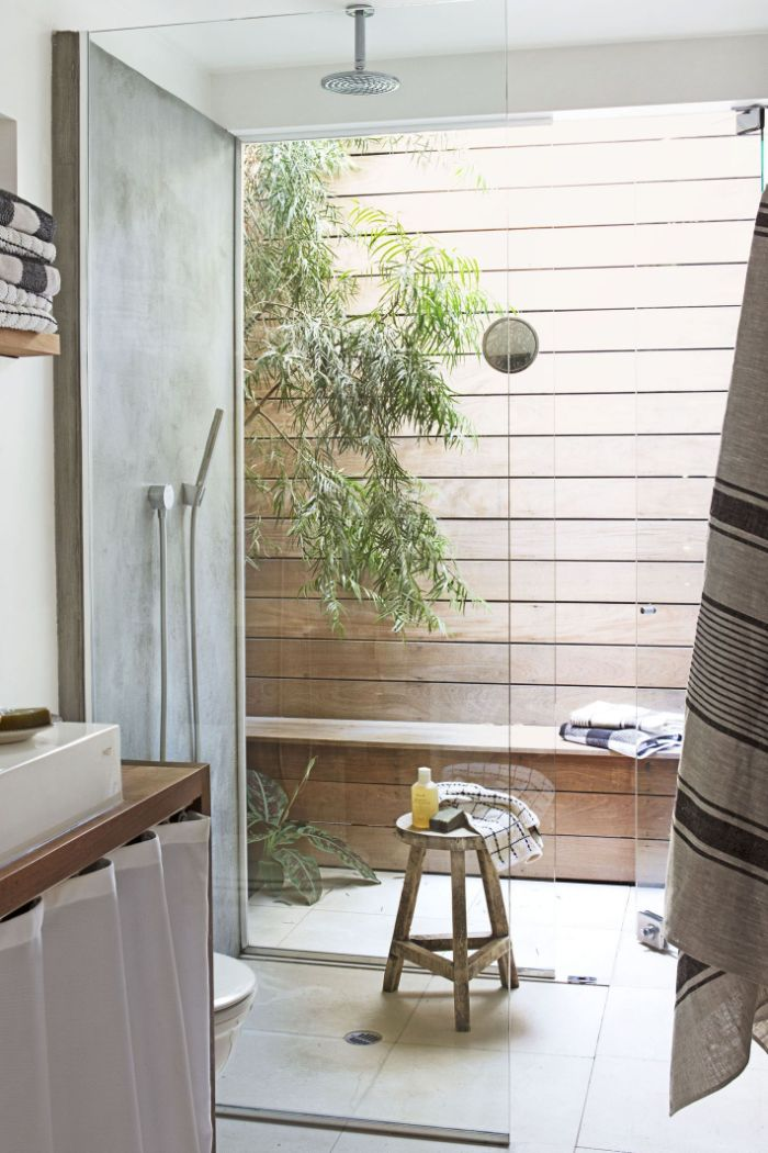 freestanding outdoor shower wood wall and bench shower next to it with tiled floor behind glass enclosure