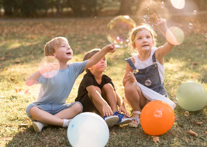 fun things to do outside three kids popping soap bubbles balloons around them