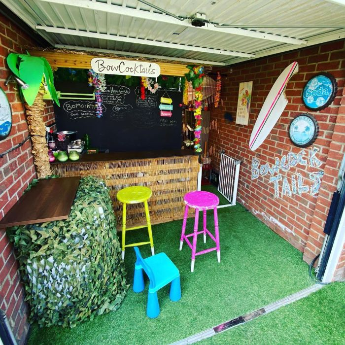 garage turned into bar with brick walls chalkboard behind the bar outdoor wooden bar yellow and pink bar stools