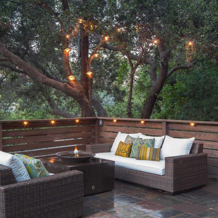 garden furniture on back patio how to hang string lights on covered patio lamps scattered on the tree above it and around the fence