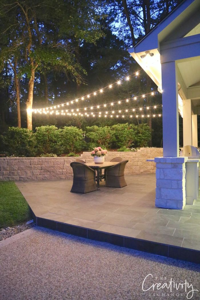 garden furniture on the back patio outdoor patio lights strings of lights hanging from a tree to the house