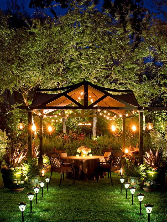 garden furniture under tent with strings of lights on the ceiling outdoor hanging lights solar lamps along the pathway