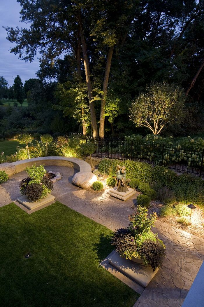 garden with lights under the plants and trees outdoor string lights stone pathway and bench