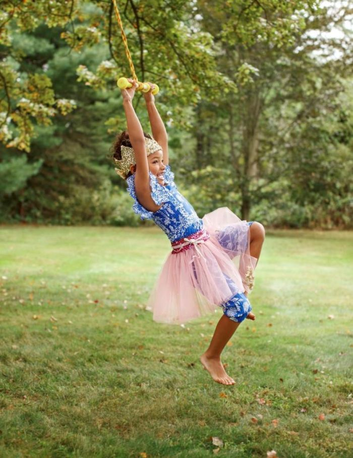 girl dressed in a princess dress with crown outdoor activities for kids swinging on a rope hanging from a tree