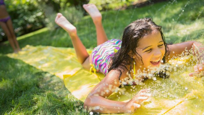 girl going down a water slide backyard games for kids plastic cloth placed on the grass