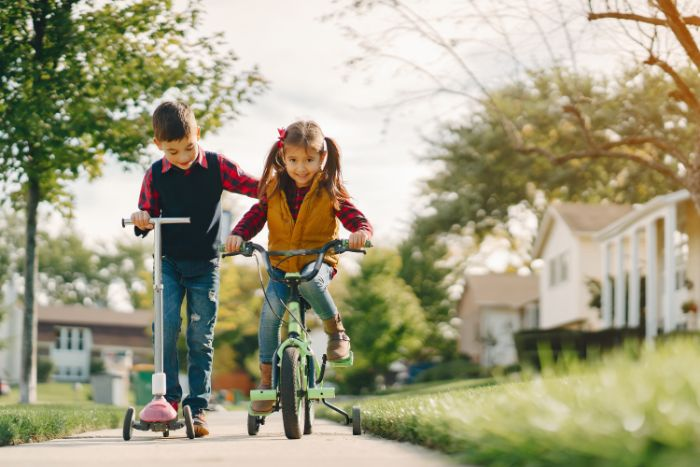 girl riding a bike outdoor activities for toddlers boy next to her riding on a scooter on the sidewalk