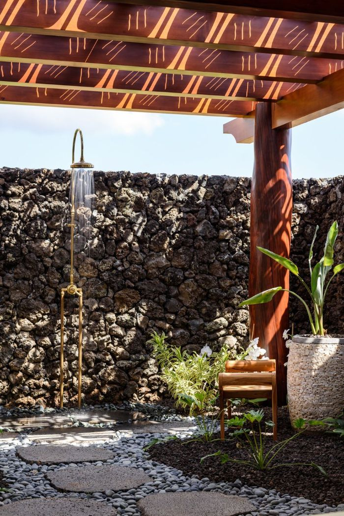 gold metal shower mounted on stone wall outdoor shower designs stone tiles and rocks on the floor