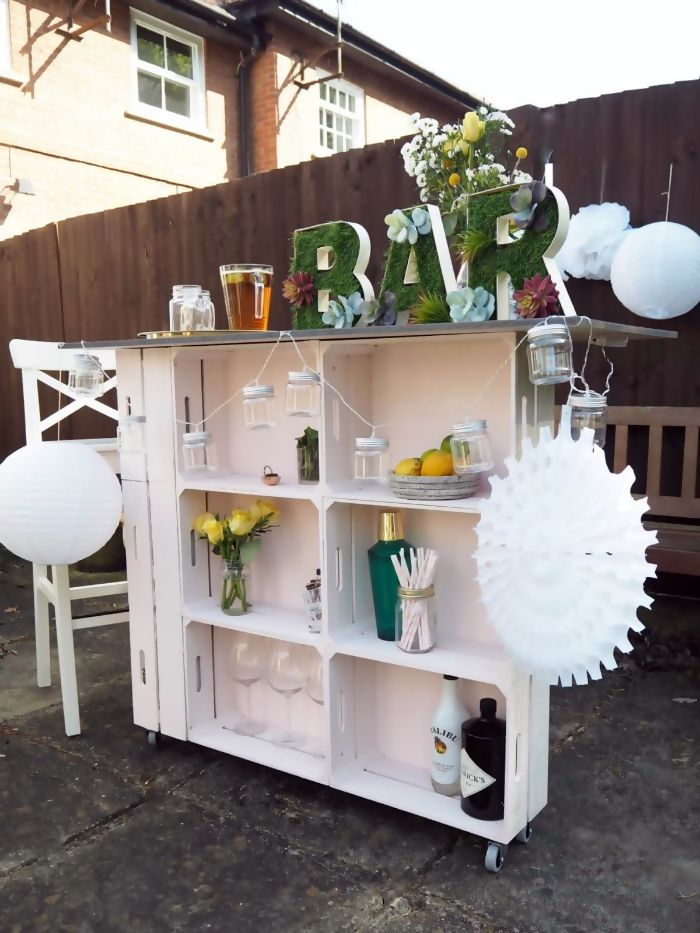 green bar sign on top of white wooden trolley made of crates home bar ideas on a budget different bottles and glasses on it
