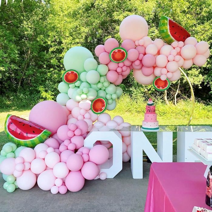 green pink white balloons forming and arch over desserts table baby shower table decorations watermelon theme