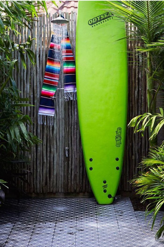 green surf on the side diy outdoor shower wall made of bamboo with colorful scarf hanging on the shower head