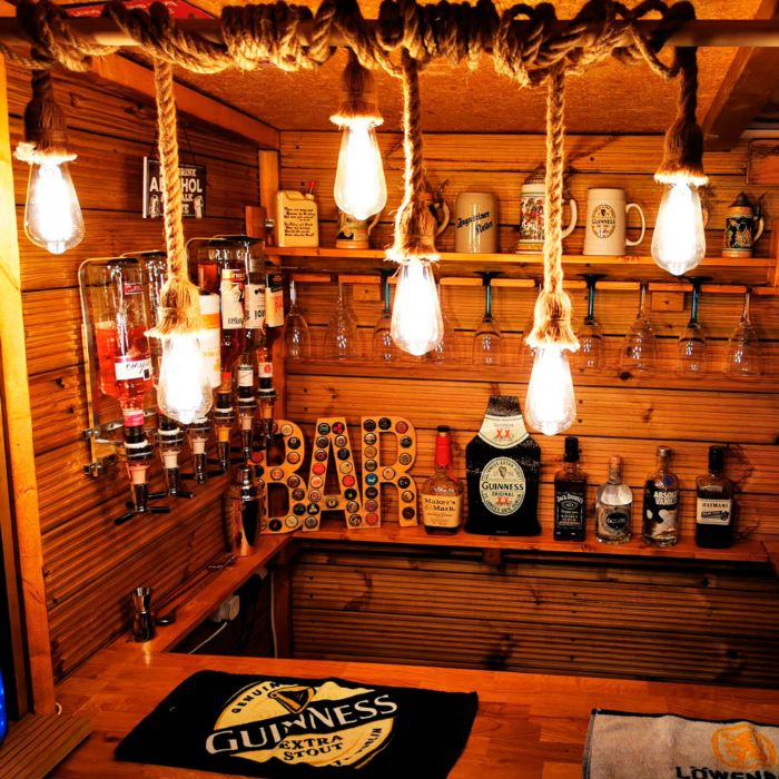 hanging lights with rope over wooden bar outdoor patio bar shelves with different alcohol and glasses
