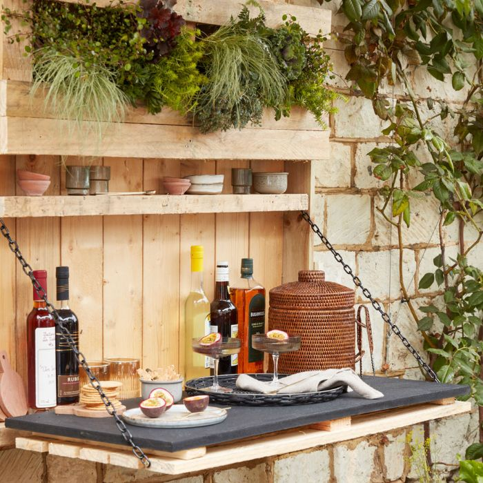 hanging wooden bar with plants backyard tiki bar different bottles and cocktail glasses on it