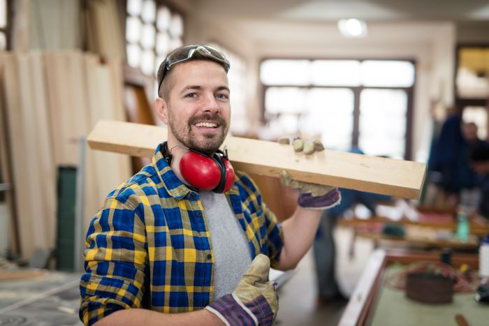 happy smiling carpenter holding wood material home remodeling wearing blue yellow plaid shirt goggles