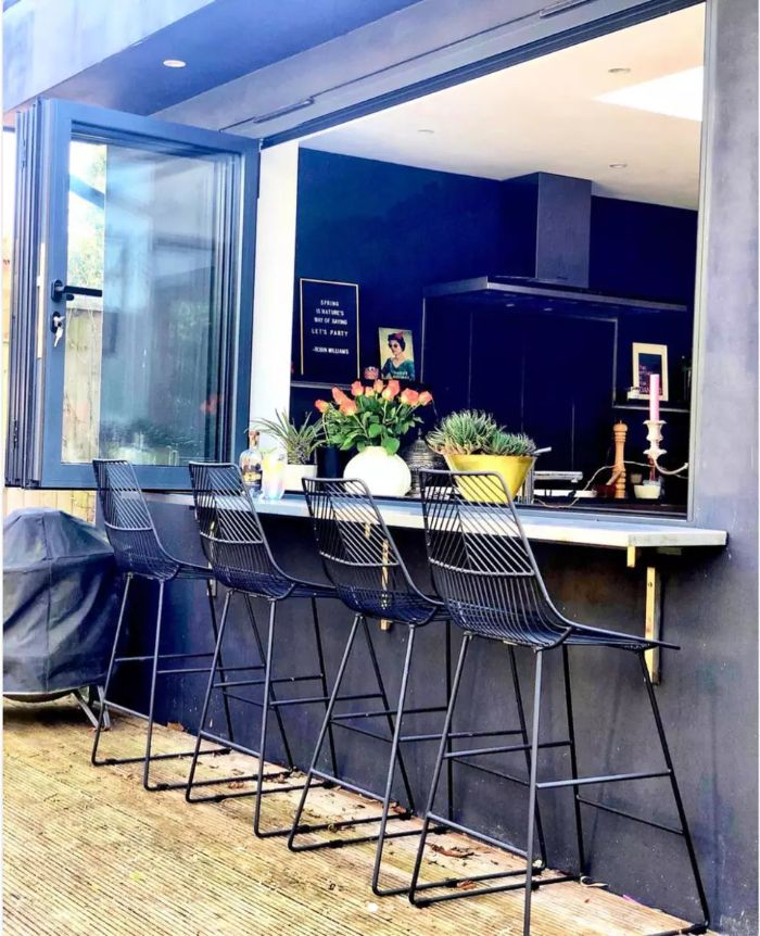 home bar ideas on a budget black metal stools next to open windows looking into kitchen