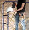 home remodeling builder handyman with construction tools in bag around his waist