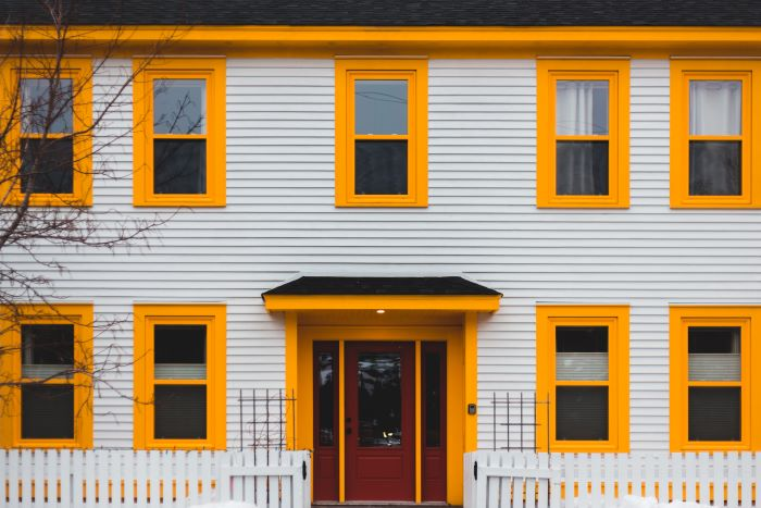 home siding white siding on house with windows with yellow frames red door