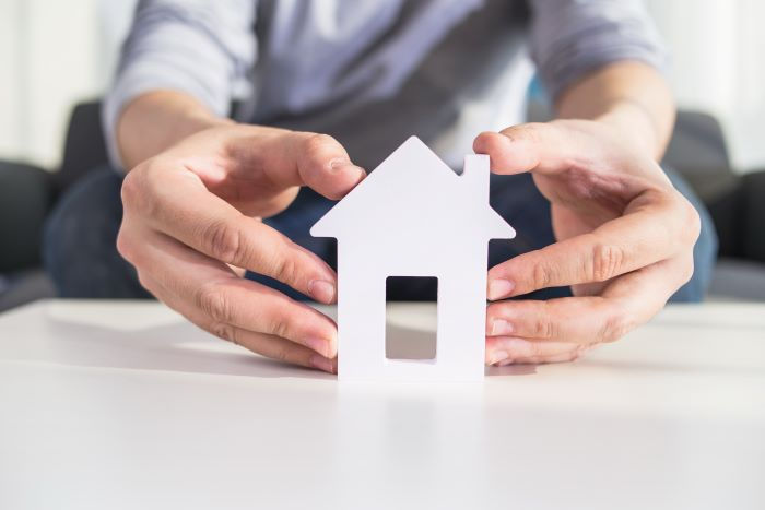 house in spain businessmen holding house model in hand placed on white surface close up photo