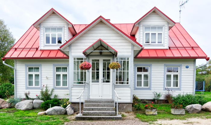 house with white siding red roof door installation large boulders in front with flower beds