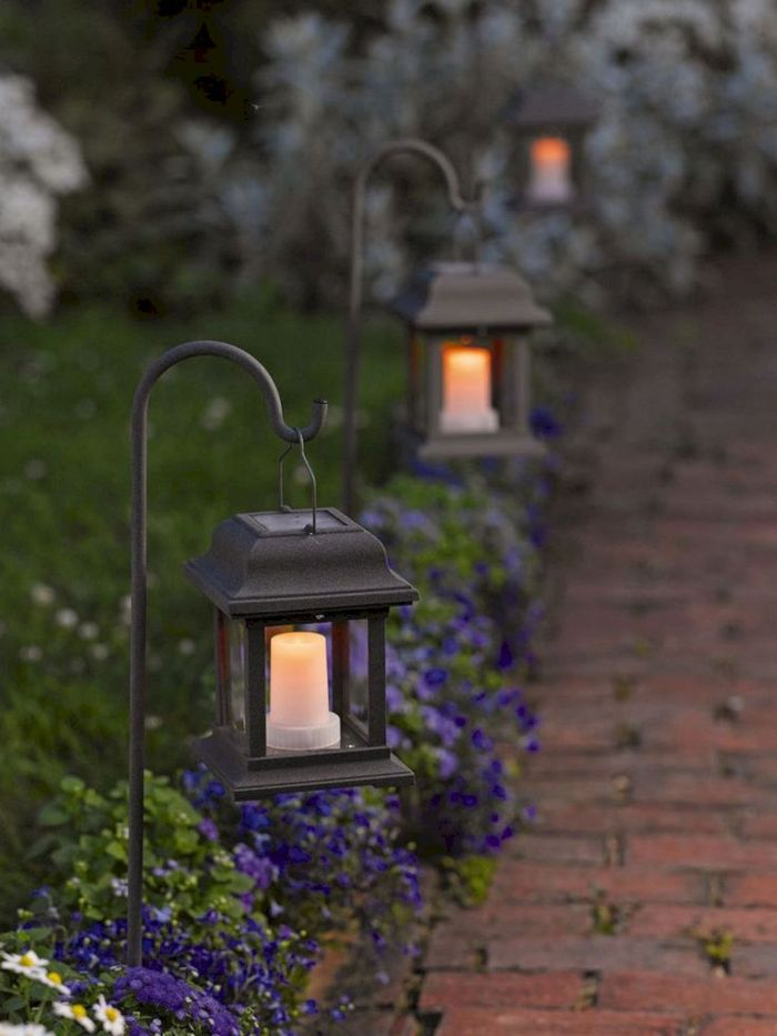 how to hang string lights on covered patio lanterns with solar candles inside hanging in the flower beds along a pathway