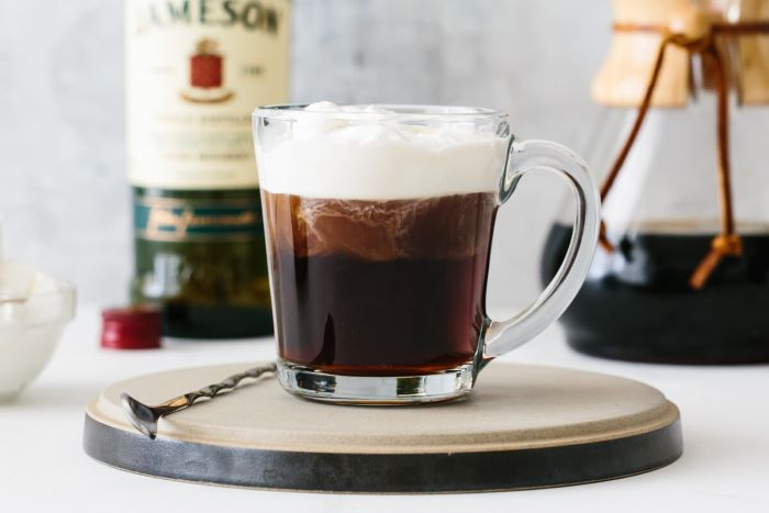 irish coffee with whipped cream on top poured in glass mug cold brew coffee spoon on the side