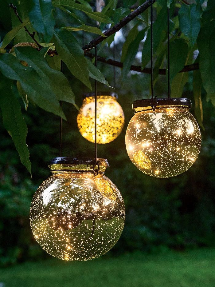 jars filled with small fairy lights outdoor string lights hanging from a tree with warm glow