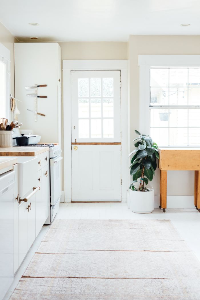 kitchen in white with door and large window on the side window installation white cabinets fridge