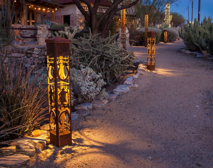 lanterns with different height and decorations placed along a pathway string light pole next to flower beds