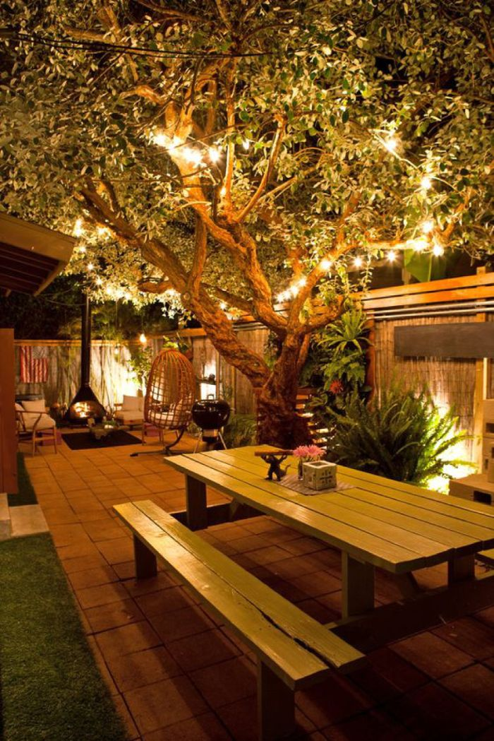 large tree wrapped with strings of lights outdoor lighting ideas wooden bench and table underneath