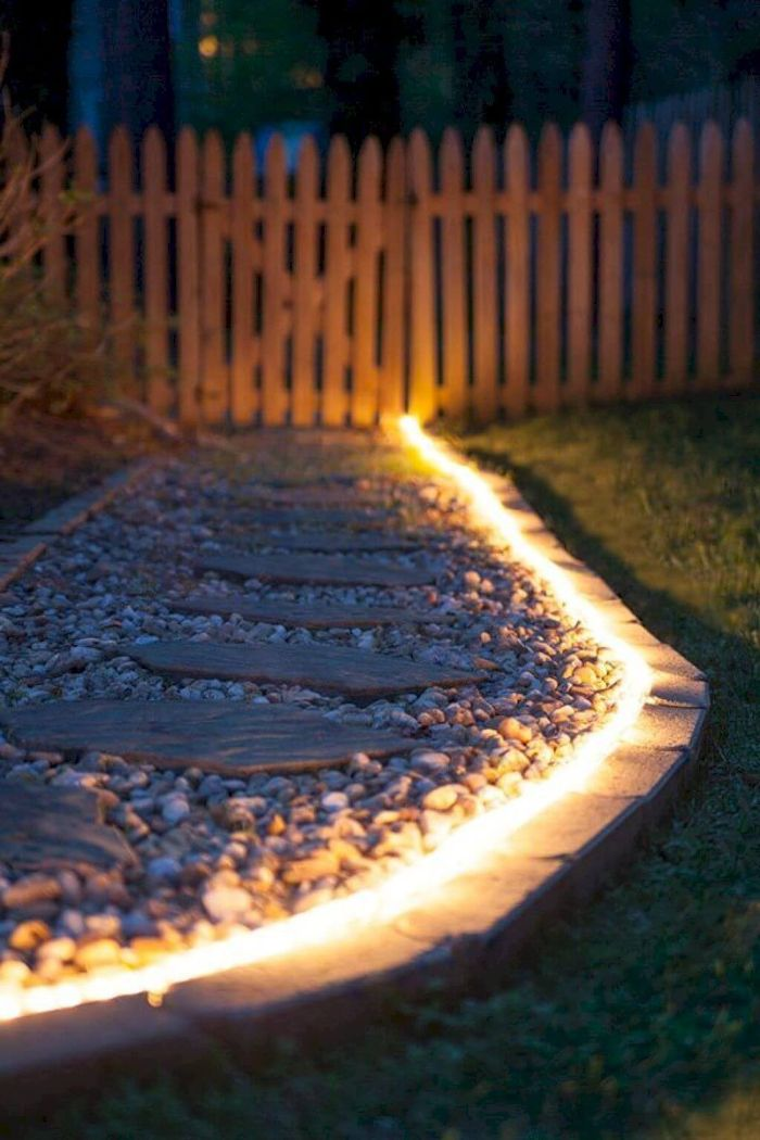 led lights hose placed along a pathway made with gravel and stones backyard lighting ideas wooden fence