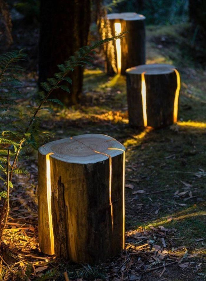 log lamps outdoor lighting ideas logs with led lights on the inside placed along a pathway next to trees