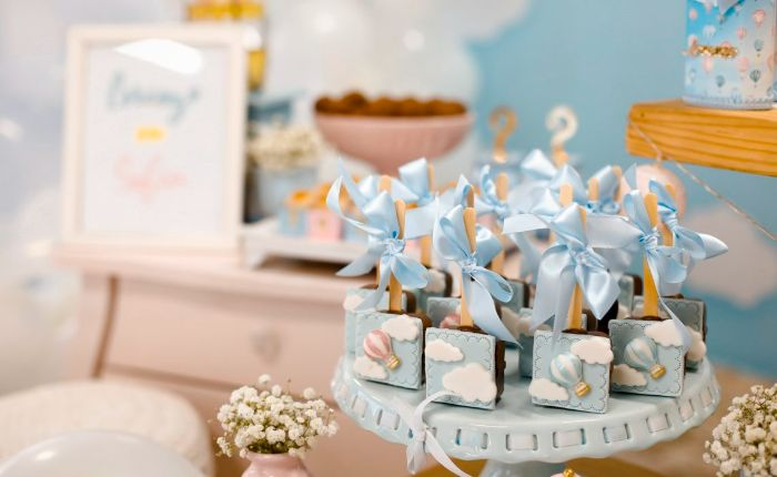 lollipops decorated with blue ribbons blue icing placed on cake stand baby shower ideas for girls hot air balloon theme