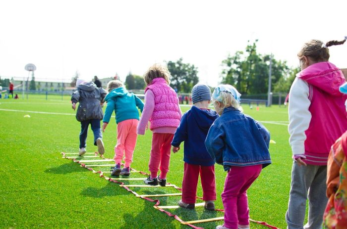 lots of kids playing on a field covered with grass outdoor games for kids ladder spread onto the grass