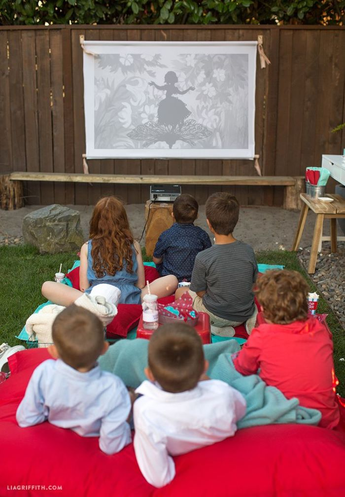 lots of kids sitting on red throw pillows with pop corn and soda fun games to play outside watching a film