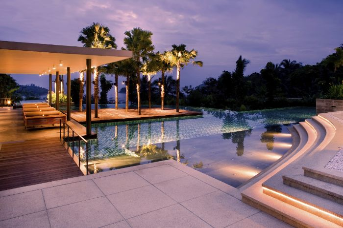 lots of lights inside a pool with deck with tall palm trees modern pool designs wooden deck with lounge chairs