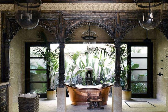 lots of plants around brass vintage bathtub on tiled floor wood outdoor shower
