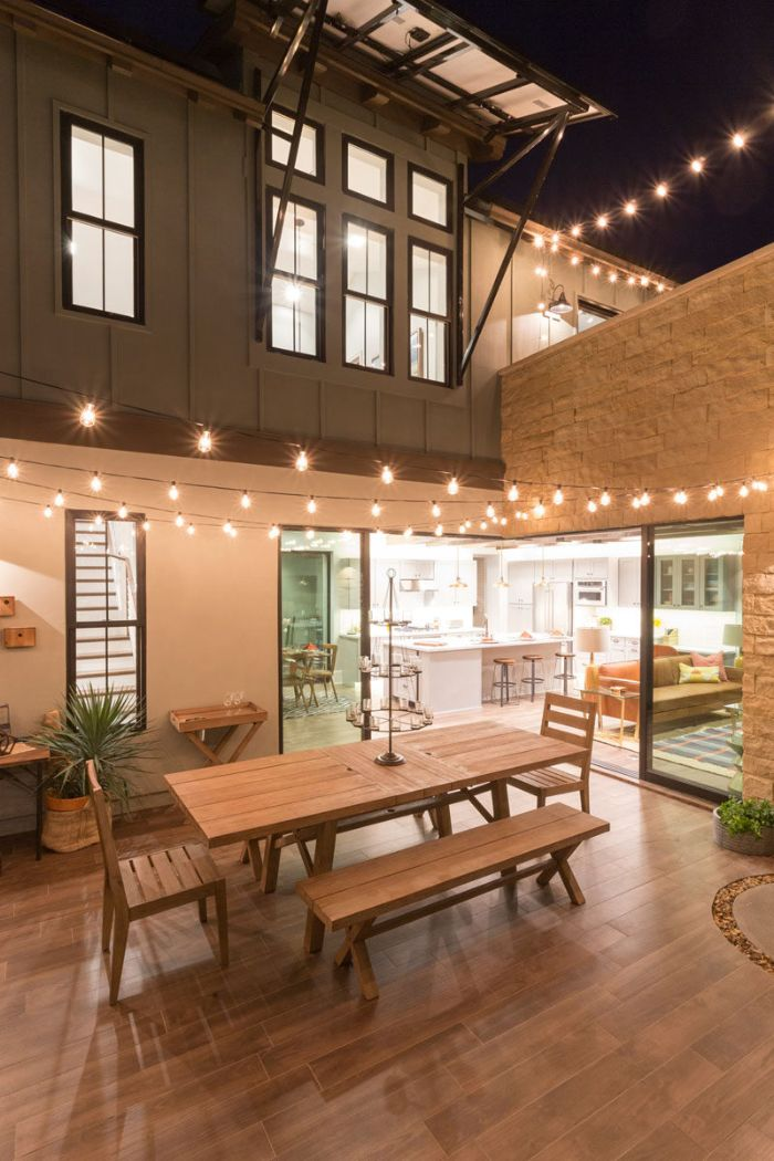 lots of strings of lights hanging above patio landscape lighting ideas wooden garden furniture