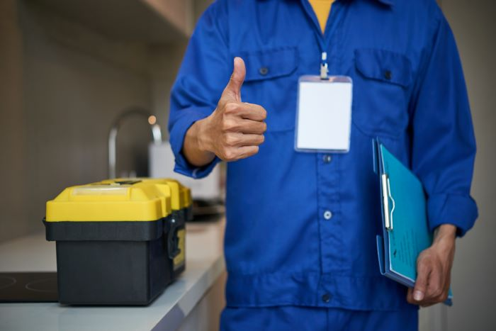 man wearing blue protective gear standing next to toolbox home remodeling holding folder