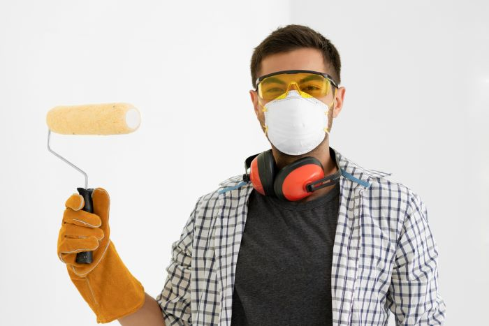 man with brown hear wearing protective equipment against lead poisoning mask glasses head set