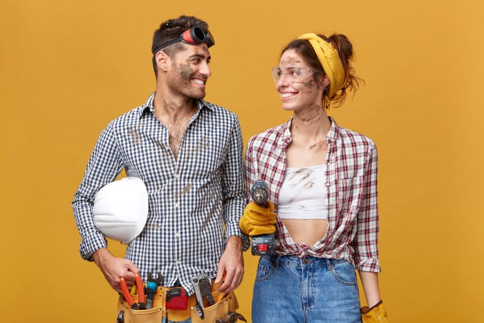 man woman wearing plaid shirts safety goggles different tools home remodeling yellow background