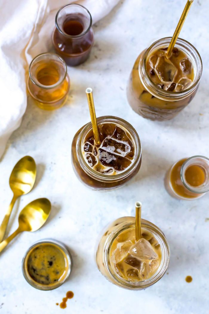 mason jars filled with coffee and ice cold brew coffee placed on granite surface