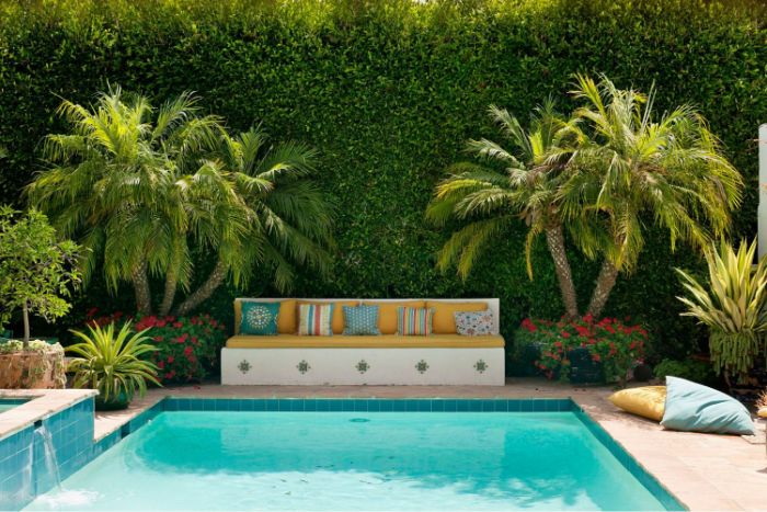 mediterranean style decor inground pool design bench with colorful throw pillows palm trees and flowers next to pool